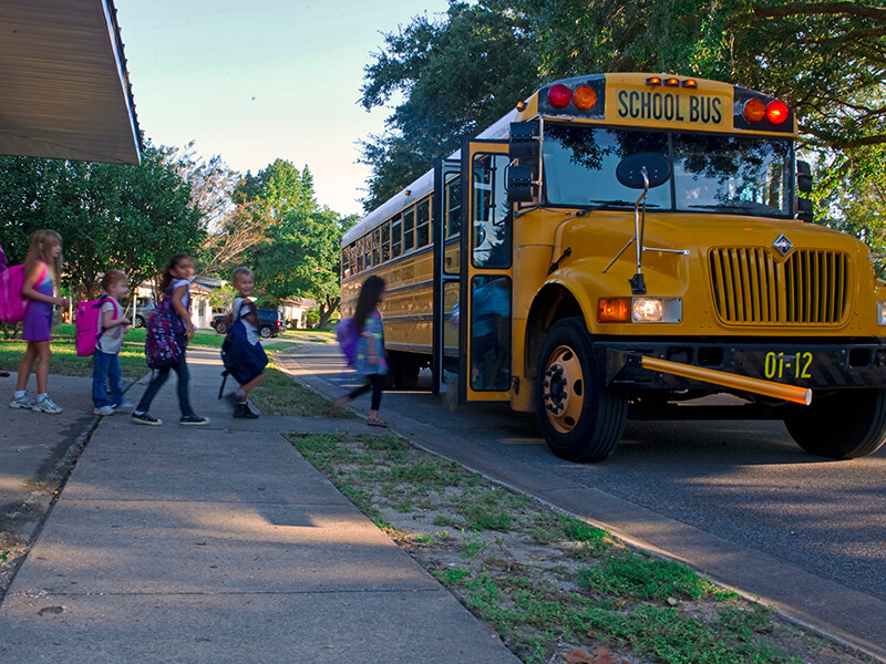 young students boarding a school bus