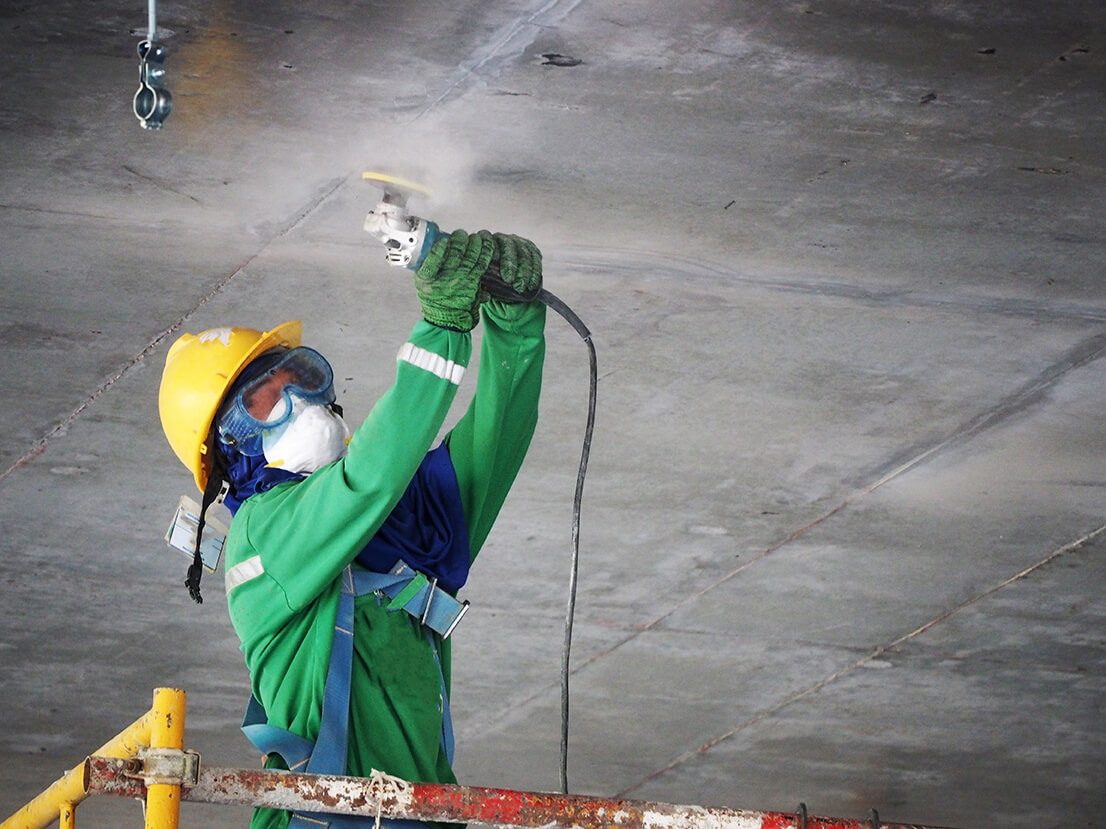 construction worker using a power grinder on concrete